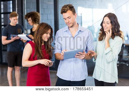 Colleagues looking at digital tablet and having a discussion in office