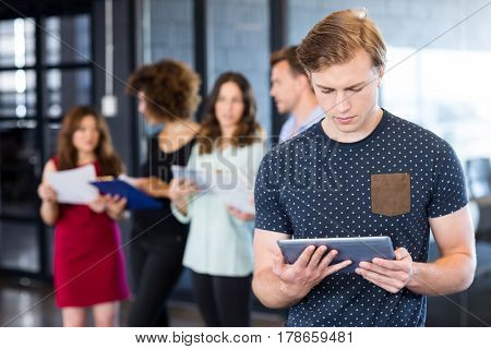 Man looking at digital tablet while her colleagues standing behind in office