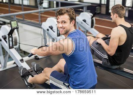 Fit men on drawing machine at gym