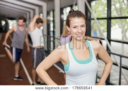 Smiling athletic woman posing with hands on hips on track