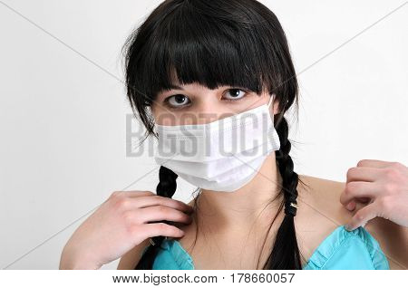 close-up portrait of young woman in protective medical mask on white background looking at camera