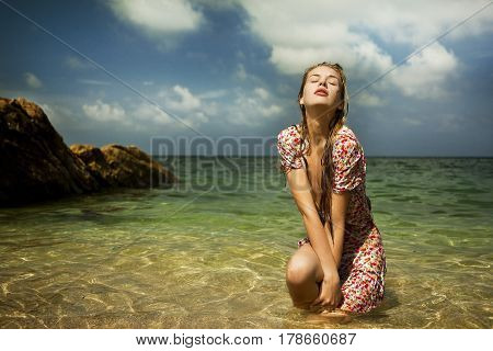 Glamour girl in a dress is awash in an ocean