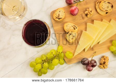 An overhead photo of glasses of white and red wine at a tasting, with cheese, bread, and grapes. Selective focus and a place for text