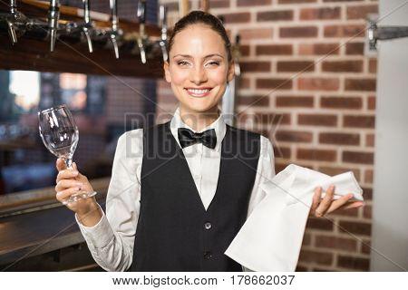 Beautiful barmaid holding shiny wine glass and towel