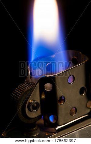 macro metal lighter petrol On black background, open fire