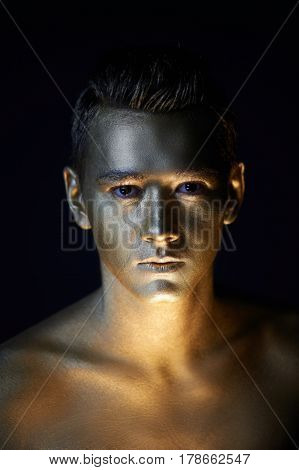 A handsome man of athletic build, completely covered in gold paint.Studio photos, With Hard lite