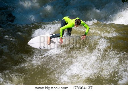 Munich Germany - June 7 2016: Boarders surfing on the Isar river in Munich Bayern Germany