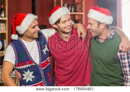 Friends with Christmas hats smiling at each other at a bar