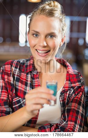 Woman smiling at camera with shot in hand inside a bar