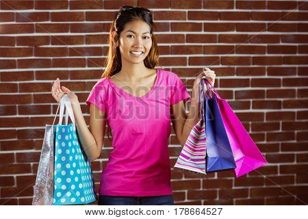 Smiling asian woman with shopping bags on brick wall