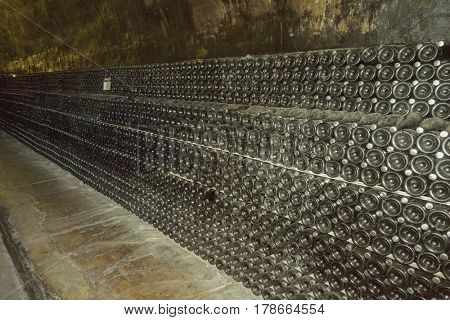 Sparkling wine is aged in bottles in a dark cellar