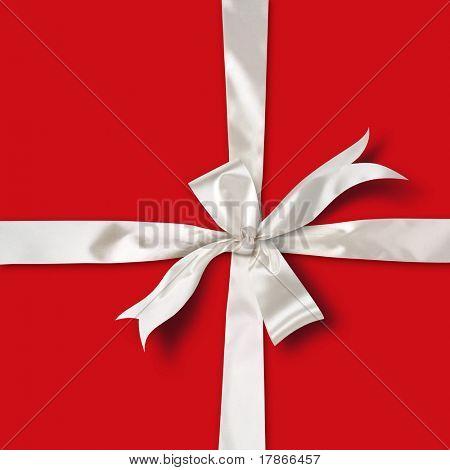 White satin ribbon over red paper gift box