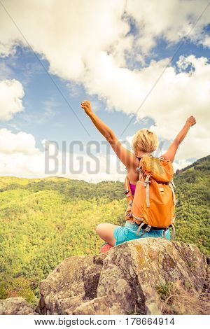 Hiking woman celebrating inspirational mountains landscape with arms outstretched. Fitness and healthy lifestyle outdoors in colorful summer nature. Trekking camping and climbing travel concept.