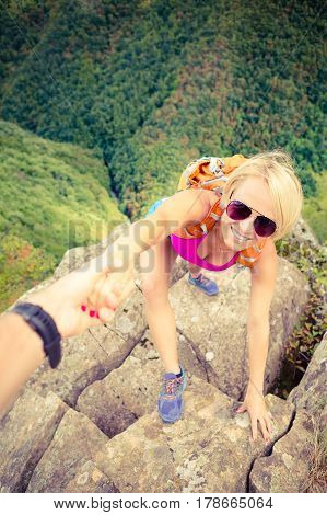 Helping hand couple hiking help each other. Man and woman climbing or hiking with motivation and inspiration beautiful inspirational landscape. Trust team in extreme sports climbing and fitness.
