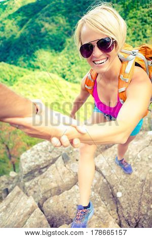 Helping hand couple hiking help each other. Man and woman climbing or hiking with motivation and inspiration beautiful inspirational landscape. Extreme sports and fitness.