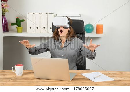 Amazed Businesswoman With Virtual Reality Headset In Workplace
