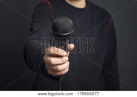 Journalist making speech with microphone and hand gesturing concept for interview. Selective focus.