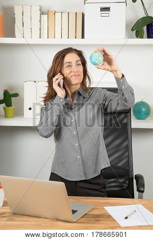Businesswoman Talking On Phone With World Globe In Hand