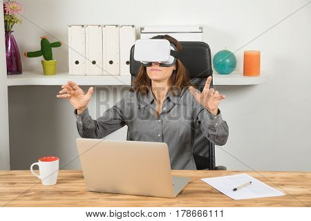 Businesswoman With Virtual Reality Headset And Laptop In Workplace