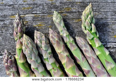 bunch of green asparagus on the old wooden plank