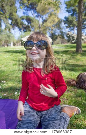 Child Playing With Adult Sunglasses In Park