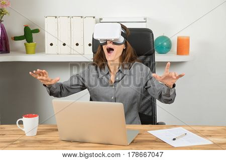 Happy Businesswoman Using Virtual Reality Headset In Workplace