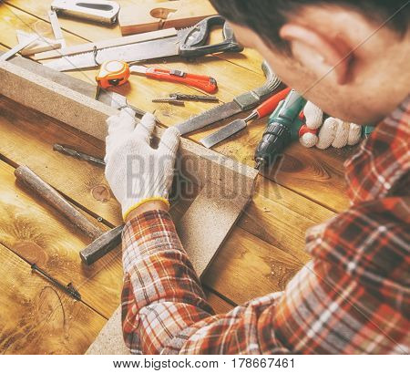 The carpenter works with wood on his workspace