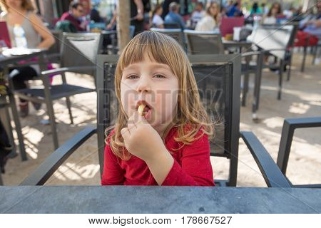 Portrait Of Child Sitting In Exterior Bar Eating Cheese Puff