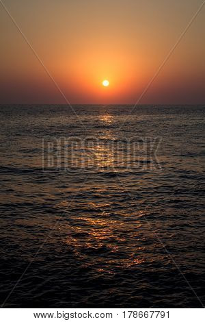 Sunset in the sea with waves from the island of Santorini.