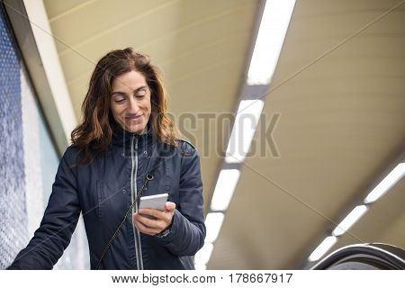 Smiling Woman In Subway Passage Reading Mobile