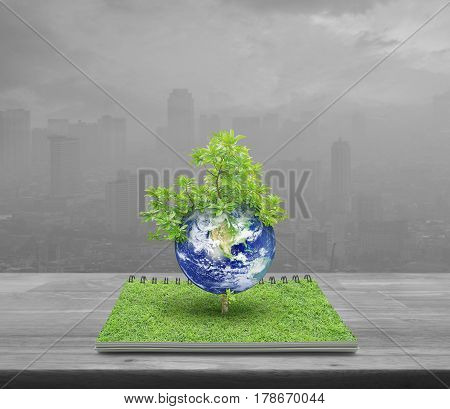 Earth with tree from an open book on wooden table over pollution city tower Ecology concept Elements of this image furnished by NASA