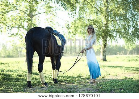 Young girl taking on a walk her dark bay stallion by the reins on stunning golden sunset. Beautiful mighty gelding horse walking and gazing on meadow field at sunny morning