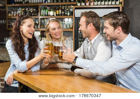 Attractive friends toasting while looking at each other in a bar