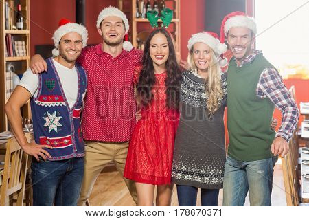 Friends wearing Christmas hats in a bar smiling at camera