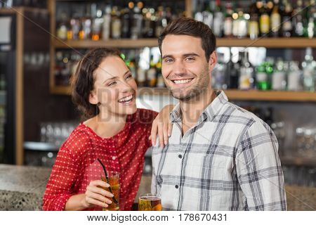 Attractive couple holding beers in a bar and man smiling at camera