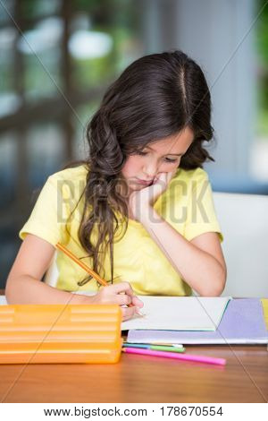 Concentrated girl studying while sitting at desk in home