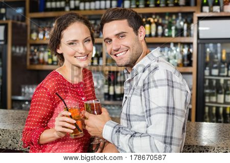 Attractive couple smiling and toasting beers
