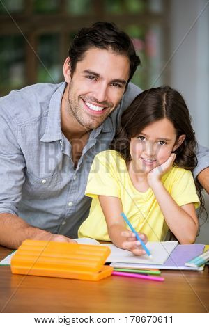 Portrait of smiling father and daughter studying at desk in home