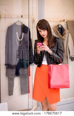Beautiful woman using her phone while window shopping in mall