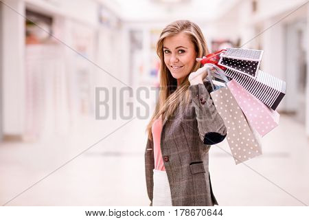 Portrait of happy woman holding shopping bags in mall