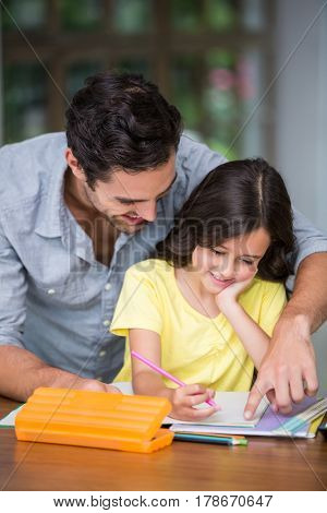 Happy father assisting daughter with homework at desk in home
