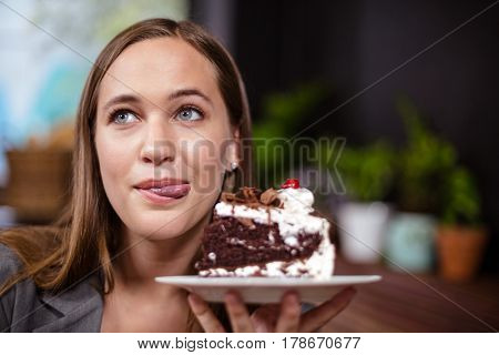 Sweet tooth woman holding piece of cake in the bar