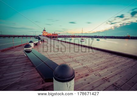 St. Kilda Pier at Dusk with boats in the harbour and Pavilion in the distance. Melbourne Australia