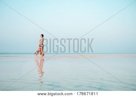 Woman In A Floral Dress Standing In Shallow Ocean Water. Girl In The Sea. Looking Into The Distance.