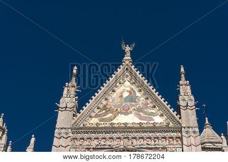 Siena Italy - September 23 2013: Upper facade mosaic Coronation of the Virgin at Metropolitan Cathedral of Saint Mary of the Assumption Siena Duomo. Siena Italy