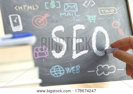 Hand writing on a blackboard in a SEO class with some icons and concepts drawn on it. Some books and school materials.