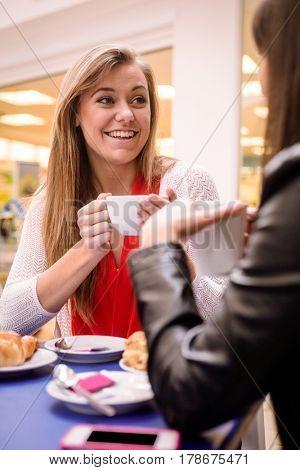 Woman talking while having coffee in coffee shop