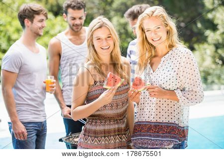 Young women smiling and having a slice of water melon while their friends preparing bbq behind