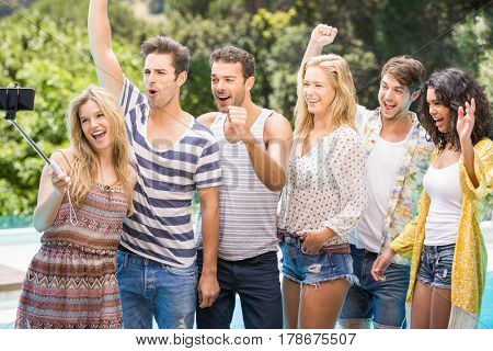 Group of friends enjoying while taking a selfie near pool