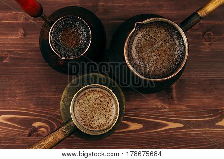 Hot coffee in shabby turkish pots cezve with tasty crema on brown old wooden board background top view. Rustic style.